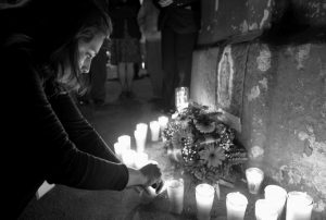 A WOMAN LIGHTS A CANDLE during a vigil in remembrance of the victims of a fire at a children's shelter, outside the morgue where the bodies are being identified in Guatemala City, Wednesday. Authorities say at least 22 girls have died after a fire at the children's shelter Virgin of the Assumption Safe Home, which was created to house children who were victims of abuse, homelessness or who had completed sentences at youth detention centers and had nowhere else to go.