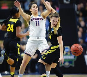 OREGON'S Sabrina Ionescu, right, tries to gather the ball after running into the defense by Connecticut's Kia Nurse during the first half of a regional final game in the NCAA women's college basketball tournament on Monday in Bridgeport, Conn.