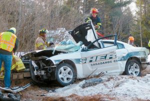 FIREFIGHTERS from Lisbon, Bowdoinham and Bowdoin fire departments work to cut free a deputy trapped in a cruiser after crashing into a tree on Route 125 in Bowdoin Saturday morning.