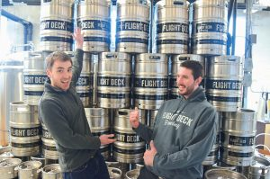 FLIGHT DECK BREWING co-owners Nate Wildes and Jared Entwisle stand next to kegs of freshly brewed beer at their location at Brunswick Landing.