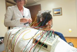 TECHNICIAN TINA WALSH puts EEG leads on Jon Obe of Dubuque, Iowa, in preparation for a sleep study at Mercy Medical Center-Dubuque's sleep lab.