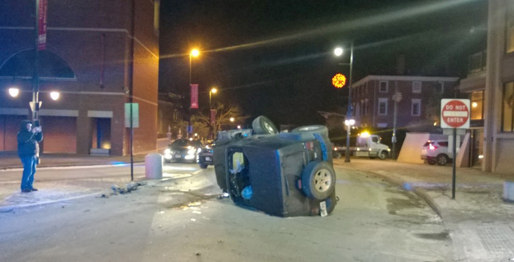 A Jeep rests on its side on High Street In Portland on Saturday night.
