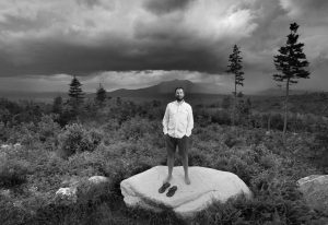 """LUCAS ST. CLAIR, son of Burt's Bees founder Roxanne Quimby, poses on land proposed for a national park in 2015. Mount Katahdin, the state's highest peak, can be seen in the background as a rainstorm passes through Baxter State Park. St. Clair said Tuesday that Gov. Paul LePage should see the land before he testifies against the monument created by former Democratic President Barack Obama at a House subcommittee hearing the following week. The governor described the land as """"cut over"""" on Monday and said it'll take decades for the land to recover."""