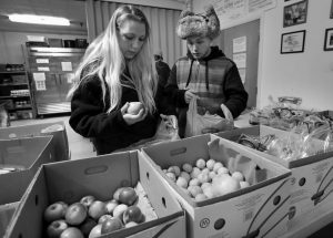 SUNNY LARSON, left, and Zak McCutcheon pick produce while gathering provisions to take home at the Augusta Food Bank in Augusta on March 27. Republican Gov. Paul LePage says his call to ban the use of food stamps for soda and candy is backed by science and a desire to reduce obesity and diabetes in the nation's oldest state.