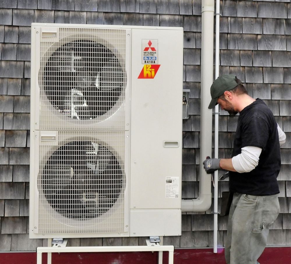 Ren Floyd of ReVision Energy installs a heat pump at the Common Ground Education Center at the Maine Organic Farmers and Gardeners Association in Unity on Monday.