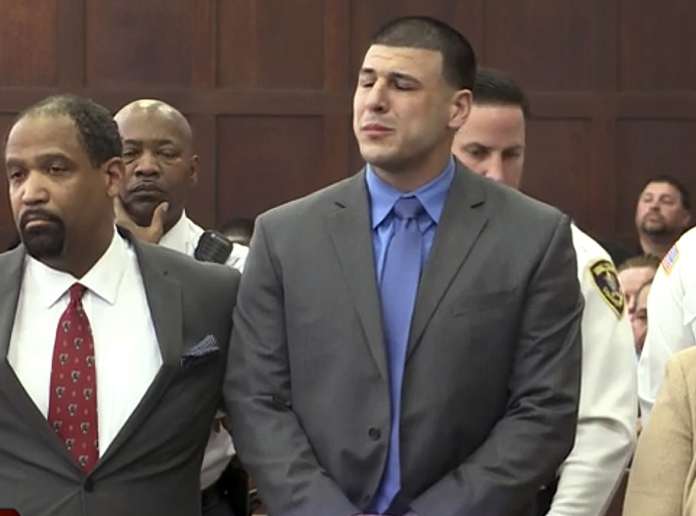 In this image from video, Aaron Hernandez, right, listens beside defense attorney Ronald Sullivan in court in Boston on Friday, as he is pronounced not guilty of murder in the 2012 shootings of two men in a drive-by shooting in Boston.