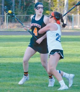 JENNA BROOKS (4) of the Dragons is pressed by Anna Manuel (23) of Mt. Ararat while looking up field.