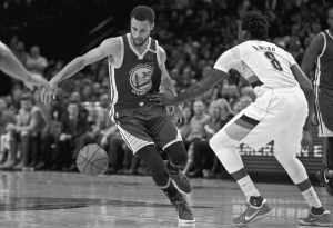 GOLDEN STATE WARRIORS guard Stephen Curry, left, dribbles around his back past Portland Trail Blazers forward Al-Farouq Aminu during the first half of Game 4 of an NBA basketball first-round playoff series on Monday in Portland, Ore.