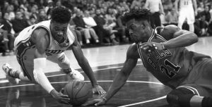 CHICAGO BULLS' Jimmy Butler, right, and Philadelphia 76ers' Richaun Holmes, left, go diving for the loose ball during the second half of an NBA basketball game on Thursday.