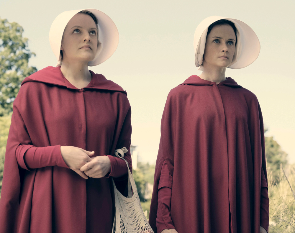 "Elisabeth Moss, left, as Offred and Alexis Bledel as Ofglen in the Hulu series ""The Handmaid's Tale,"" based on the novel by Margaret Atwood."