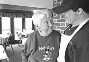 ROSE GRONEMEYER talks with resident Scott Walters at the restaurant at the Village of the Blue Rose in Clarksville, Missouri.