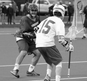 """GABE PALIZAY of the Brunswick High School boys lacrosse team eyes Connor Brown (15) of Mt. Ararat on defense during Monday's """"Battle of the Bridge"""" game at Bowdoin College on Monday. Palizay and the Dragons won, 13-8."""