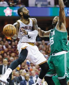 CLEVELAND'S Kyrie Irving (2) passes around Boston's Marcus Smart (36) during the second half of Game 4 of the NBA basketball Eastern Conference finals on Tuesday in Cleveland.