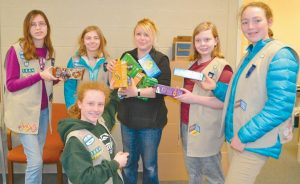 UNDER THE GUIDANCE OF TROOP LEADERS Dawn Grimes and Gladys Szabo, Girl Scout Troop 1644 recently delivered over 200 boxes of Girl Scout cookies to Spectrum Generations' local Meals on Wheels recipients through their cookie share program. The Girl Scouts are pictured here with Meals on Wheels coordinator Casey Henson, center. More than 30,000 meals were delivered last year in the greater Brunswick area by volunteer drivers. The meals are prepared by Spectrum Generations at their Cohen Center in Hallowell, brought to the People Plus Center on Union Street, and then distributed by the volunteer drivers to over 140 recipients. For more information on Meals on Wheels visit spectrumgenerations.org; for more information on People Plus visit peopleplusmaine.org.