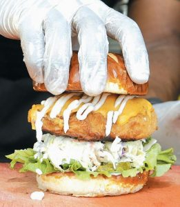 A HANDLER tops a Krispy Fried Chk'n sandwich with a doughy pretzel bun in Miami. The fare is popular among vegans and vegetarians who long for greasy comfort food, but abstain for ethical reasons.