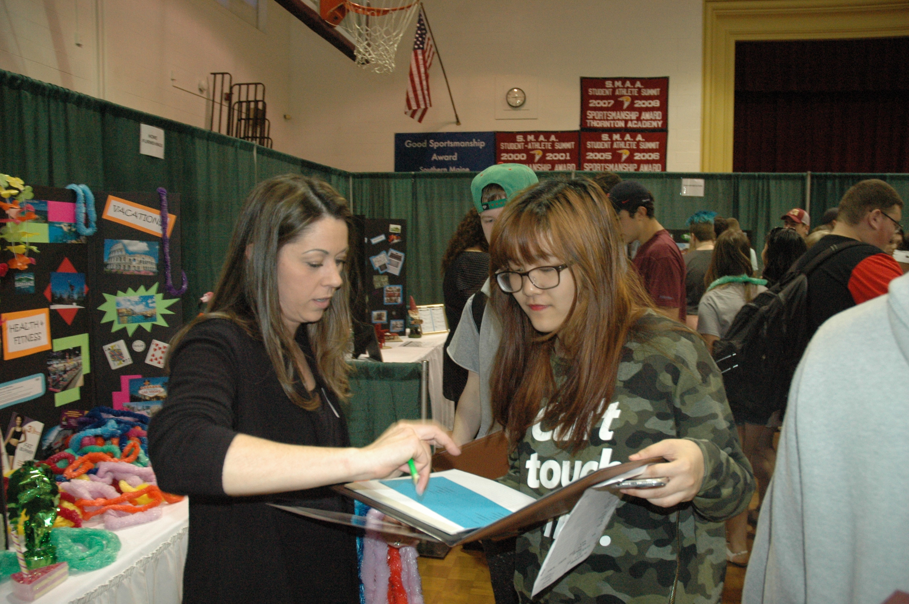 Shari Smith, payment services manager with PeoplesChoice Credit Union, talks to Thornton Academy student Ina Vu at a Financial Fitness Fair at the school on Wednesday. LIZ GOTTHELF/Journal Tribune