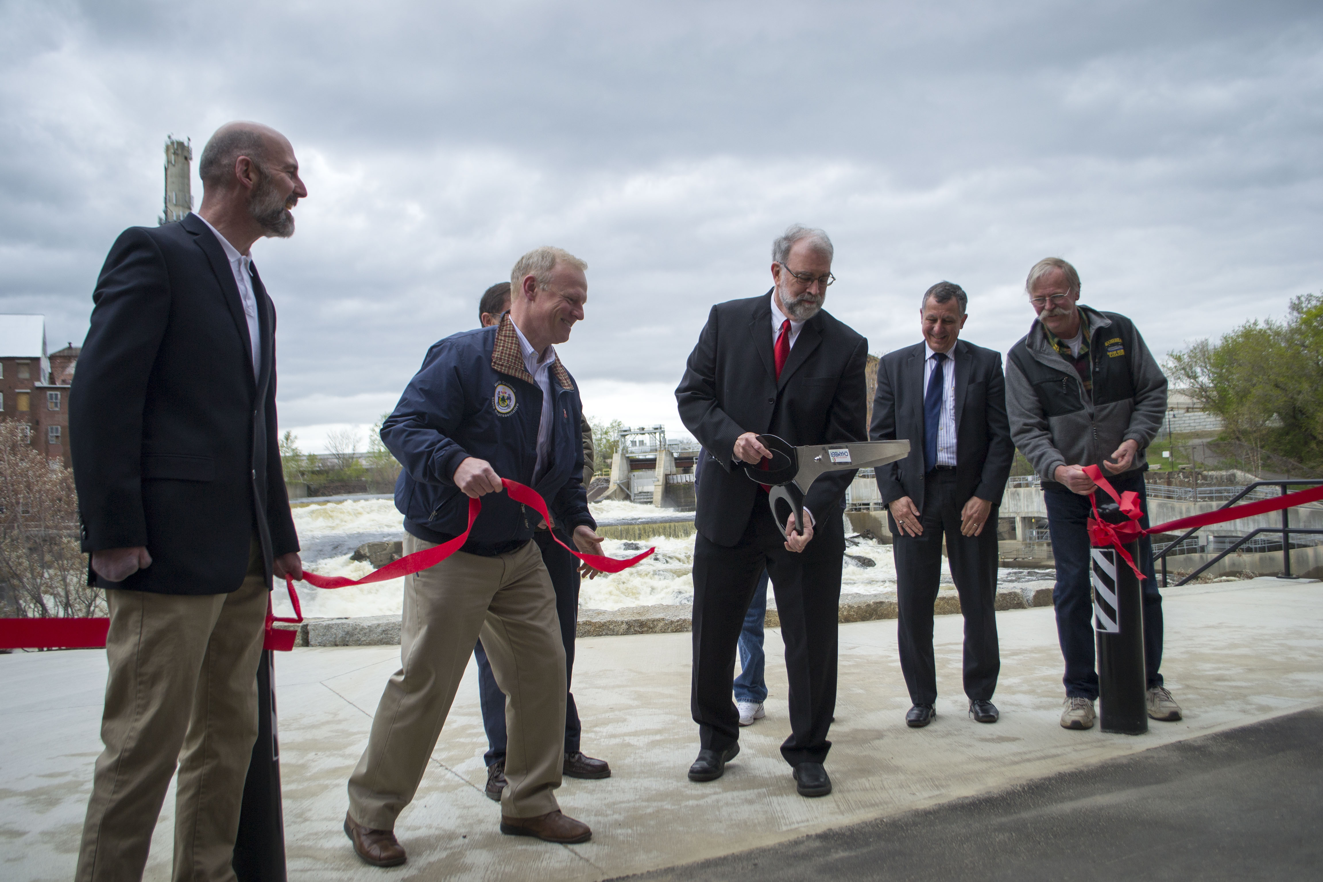 Biddeford Mayor Alan Casavant, center, and other city and state officials cut the ribbon on the new Laconia Plaza, located along the city's RiverWalk on Thursday. From left: Brad Favreau, Marin Grohman, Casavant, Norman Belanger and Michael Swanton. ALAN BENNETT/Journal Tribune