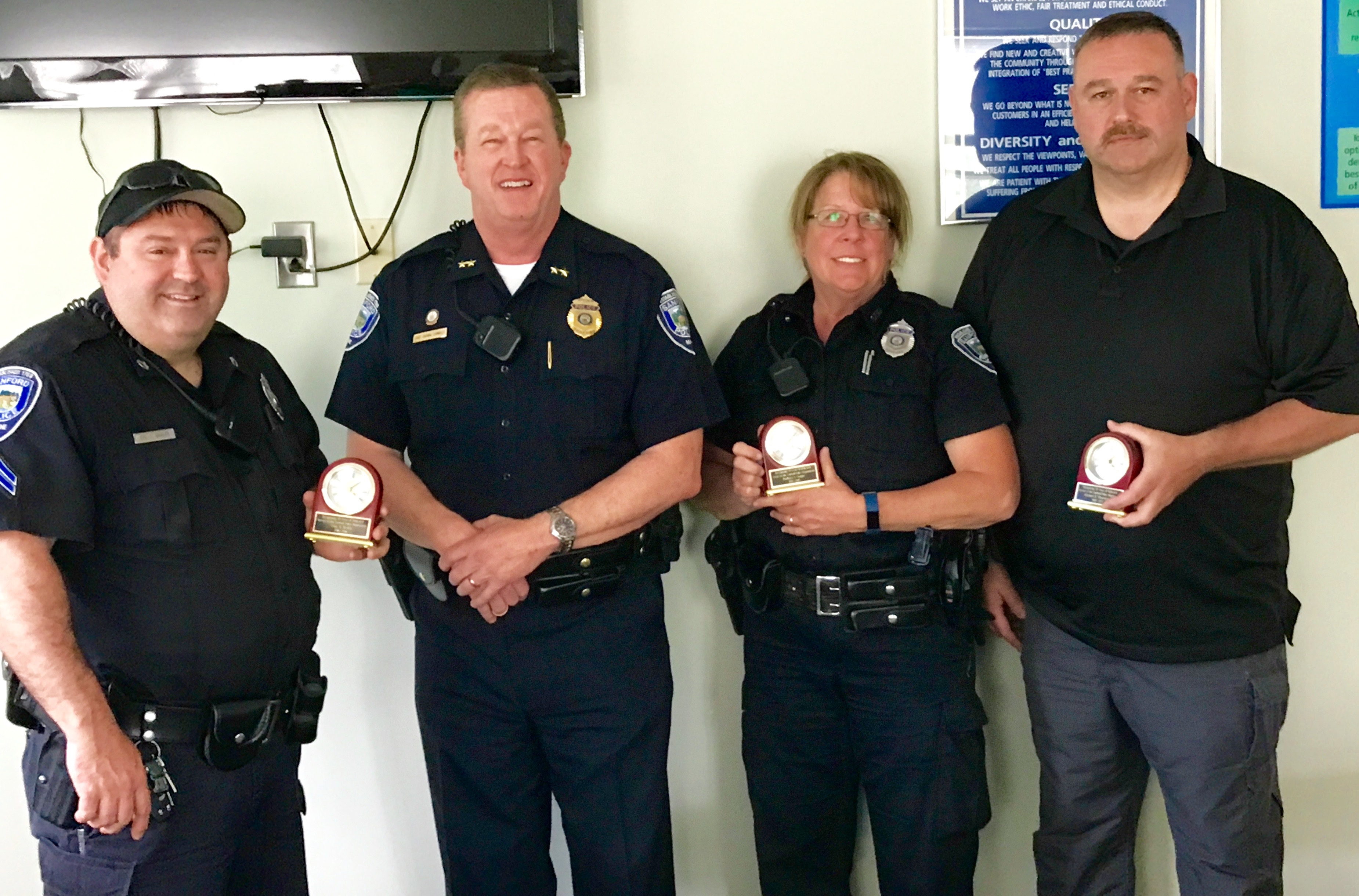"""Sanford Police paused  to recognize three longtime officers whom — as of May 24 —have  a combined total of 94 years, six months, five weeks and six days with the department. Recognized by Police Chief Tom Connolly, second from left, with commemorative clocks were, from the left, Corporal Troy Braley, Connolly,  Officer Barbara """"Amy"""" Gagne and School Resource Officer Michael """"Tipper"""" Thornton.  COURTESY PHOTO/Sanford Police"""