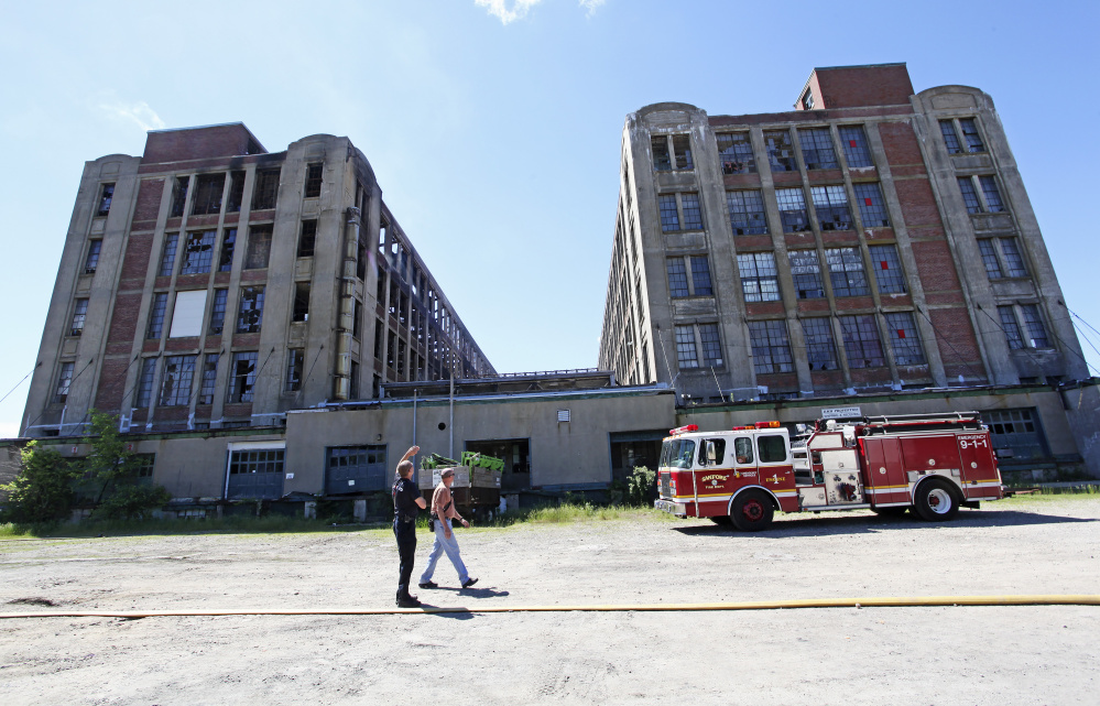 Sanford Fire Chief Steve Benotti and firefighter Todd Levesque keep an eye on hot spots Sunday at the Stenton Trust Mill Complex.
