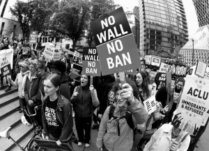 PROTESTERS WAVE SIGNS AND CHANT during a demonstration against President Donald Trump's revised travel ban, outside a federal courthouse in Seattle, on May 15. The Supreme Court is letting the Trump administration enforce its 90- day ban on travelers from six mostly Muslim countries, overturning lower court orders that blocked it. The action Monday is a victory for President Donald Trump in the biggest legal controversy of his young presidency.
