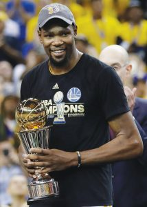 GOLDEN STATE WARRIORS forward Kevin Durant smiles as he holds the Bill Russell NBA Finals Most Valuable Player Award after Game 5 of basketball's NBA Finals between the Warriors and the Cleveland Cavaliers in Oakland, Calif., on Monday. The Warriors won, 129-120, to win the NBA championship in five games.