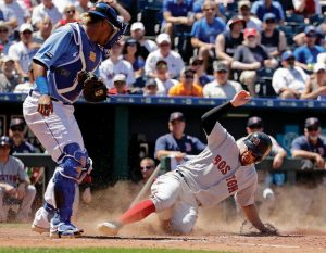 BOSTON'S Deven Marrero beats the tag by Kansas City Royals catcher Salvador Perez to score on a catching error by first baseman Cheslor Cuthbert during the fifth inning of a baseball game on Wednesday in Kansas City, Mo.