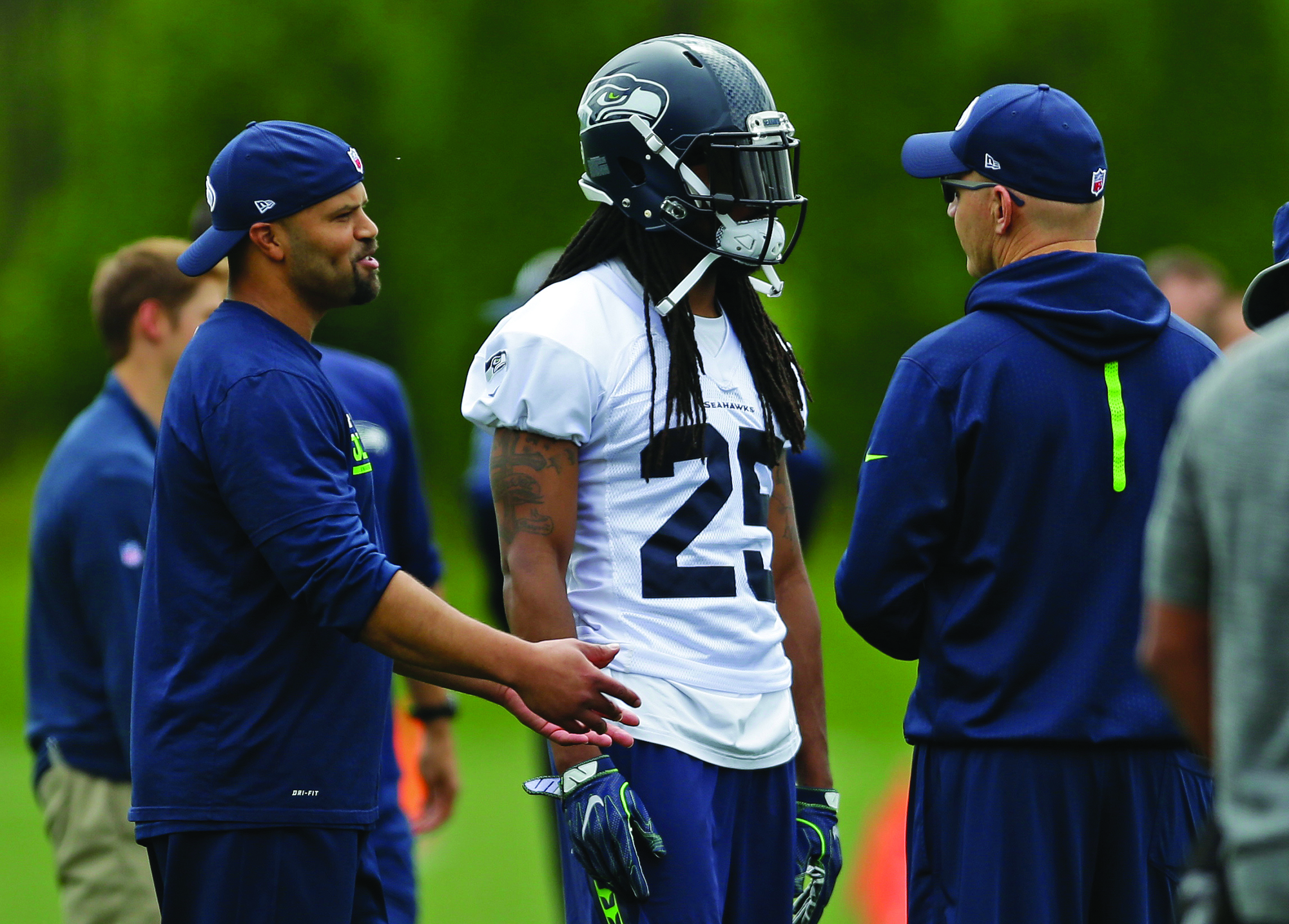Seattle Seahawks cornerback Richard Sherman (25) talks with offensive coordinator Darrell Bevell, right, and defensive coordinator Kris Richard, left, during NFL football practice on Tuesday in Renton, Wash. AP NEWSWIRE