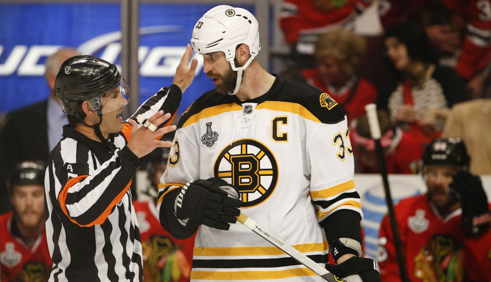 Wes McCauley, going over a situation with Boston Bruins defenseman Zdeno Chara, was a minor league player who still suits up for local pickup games.