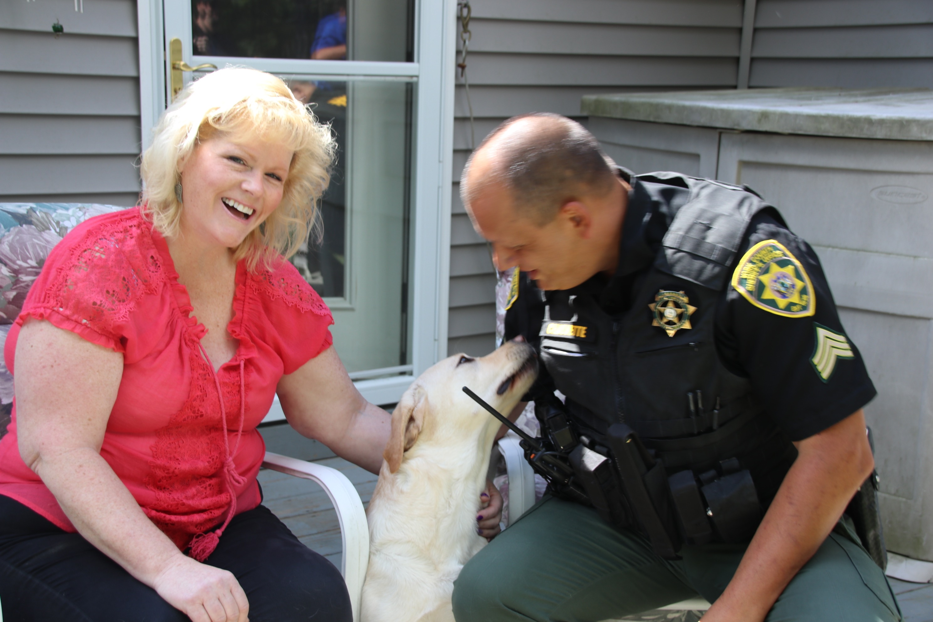 Addie, a 3 1/2 year old Labrador retriever, gives York County Sheriff's Office Sgt. Dave Chauvette a snuggle Friday morning while her owner, Leslie Reynolds, looks on. Chauvette stepped in and administered Narcan to the dog after she accidentally ingested oxycodone Thursday morning. TAMMY WELLS/Journal Tribune