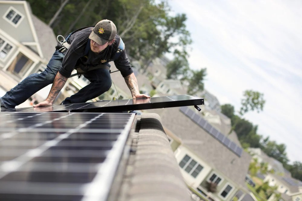 Jack Doherty, photovoltaic project manager for Portland-based ReVision Energy, installs a solar panel on a home at OceanView in Falmouth. The company, which employs almost 200 people, has installed panels on about 50 roofs within the development.