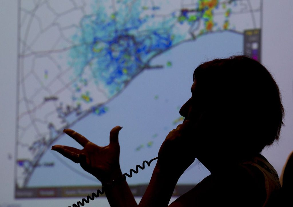 A map of the Texas coast is projected on a screen Thursday as Deb Nowinski, a disability integration coordinator  in the Galveston County Office of Emergency Management, gives information to a caller regarding the approach of Hurricane Harvey.
