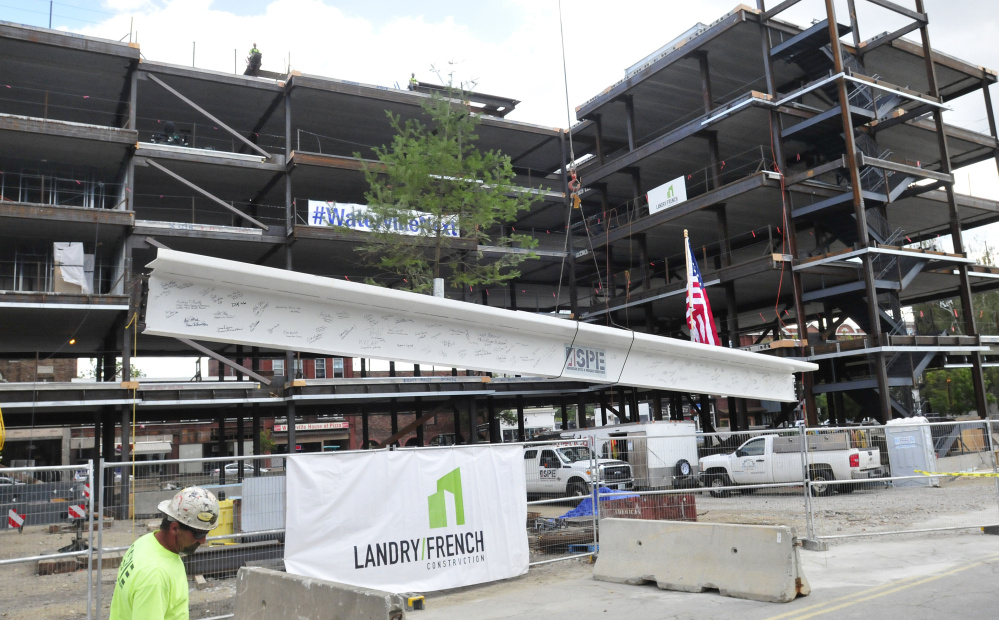 The final beam of the Colby College downtown dormitory, which will include retail and community spaces, rises to top off the building's frame Thursday during a ceremony in Waterville.