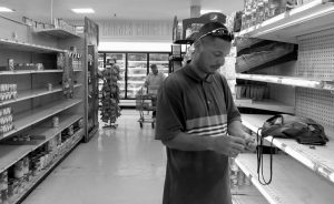 CHRISTIAN MENDOZA counts money in the aisle of a supermarket where he had hoped to buy water but only found cans of juice in San Juan, Puerto Rico, Monday. Bottled water was gone from stores throughout Puerto Rico in the few stores open five days after the earthquake.