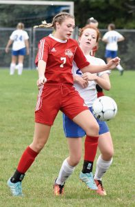WISCASSET'S Vanessa Dunn (7) battles Oak Hill's Sadie Waterman for possession of a bouncing ball during the Raiders' 4-1 MVC win in Wales on Monday.