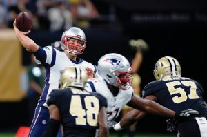 NEW ENGLAND PATRIOTS quarterback Tom Brady (12) passes under pressure from New Orleans Saints strong safety Vonn Bell (48) and defensive end Alex Okafor (57) in the first half of an NFL football game in New Orleans on Sunday.