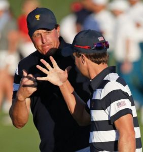PHIL MICKELSON, left, fist bumps partner Kevin Kisner, right, on the 17th hole during the Presidents Cup foursomes golf matches at Liberty National Golf Club in Jersey City, N.J., on Thursday.
