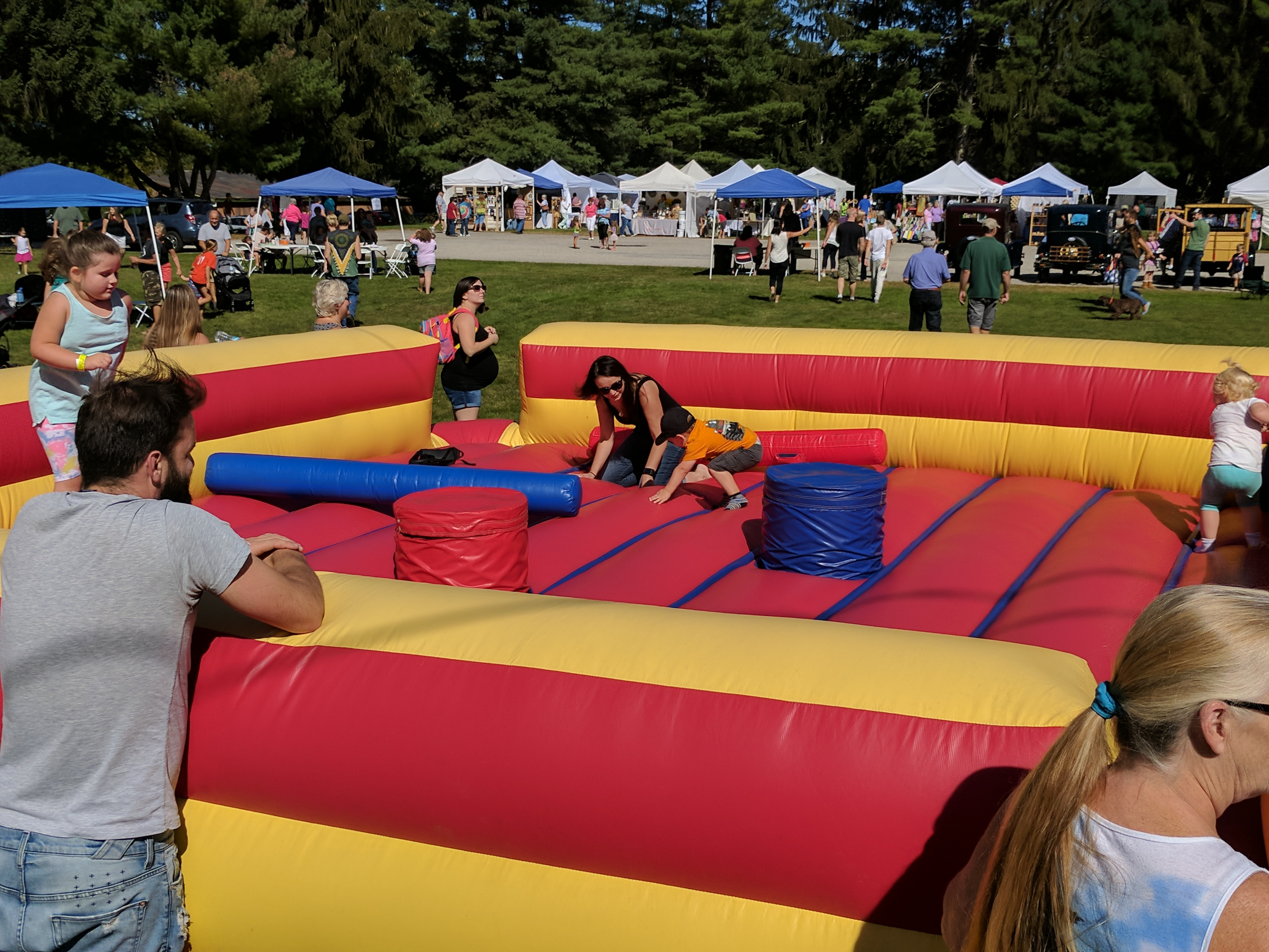 Parents watch their children as they play in the kids' zone at the Alfred Apple Festival at Shaker Hill in Alfred on Saturday. Thousands flowed through over Saturday and Sunday to stop by the festival. RYDER SCHUMACHER/Journal Tribune