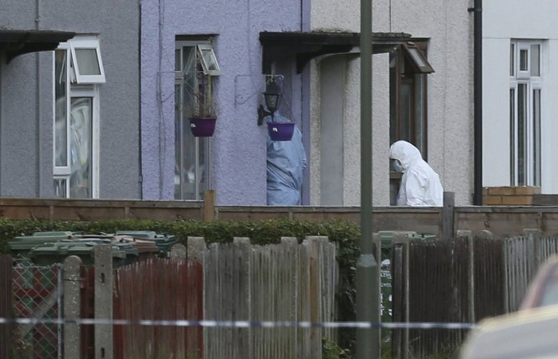 Police forensics officers enter a property in Sunbury-on-Thames on Saturday seeking evidence connected to Friday's subway bombing in London. AP NEWSWIRE/Johnathan Brady, PA via AP