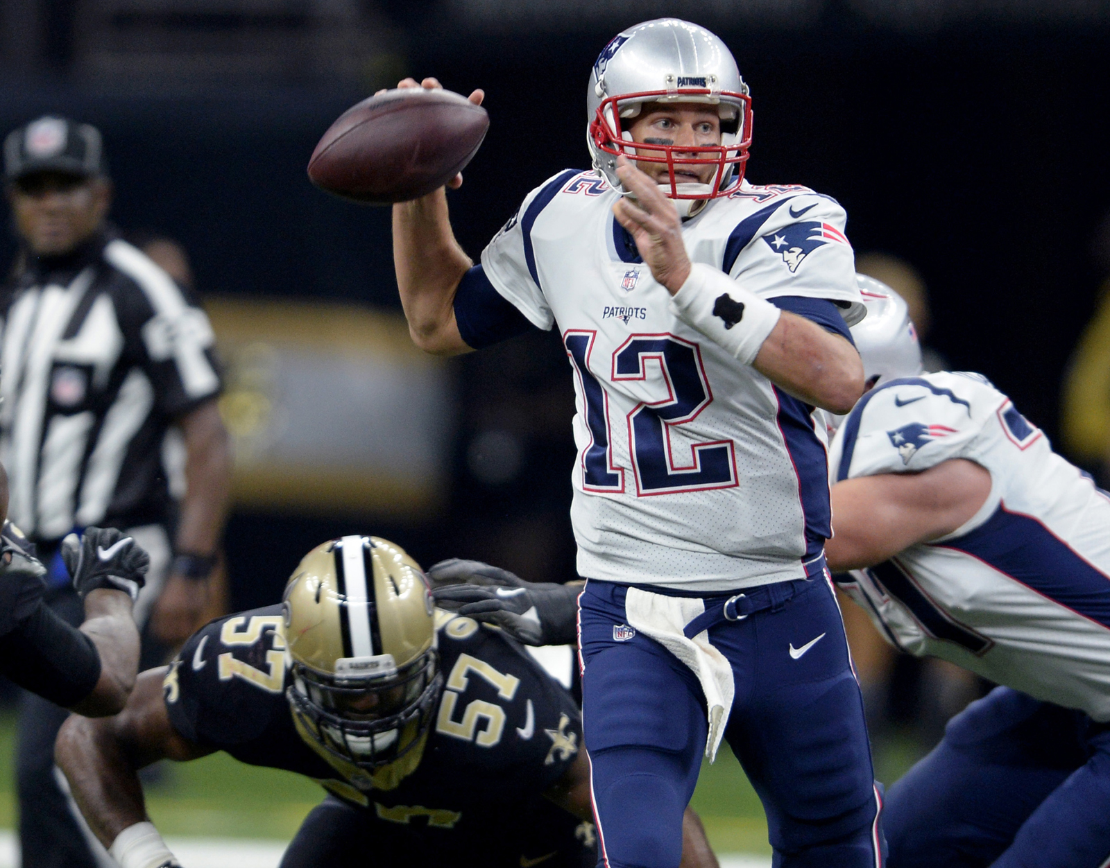 New England Patriots quarterback Tom Brady (12) passes under pressure from New Orleans Saints defensive end Alex Okafor (57) in the first half of an NFL football game in New Orleans, Sunday. AP NEWSWIRE