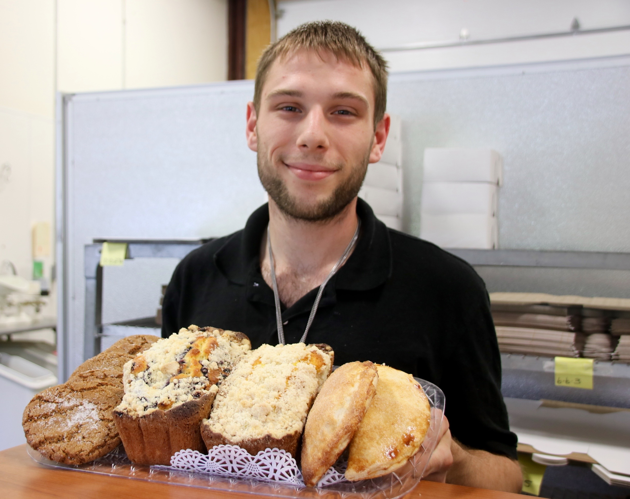 Ben Dube, who purchased New England Bakery in south Sanford in December,  holds a tray with a small sampling of the baked goods he and another baker turn out daily for an array of commercial accounts. Recently, New England Bakery began delivering baked goods — particularly donuts — to residents in Sanford and Springvale on the weekends. TAMMY WELLS/Journal Tribune