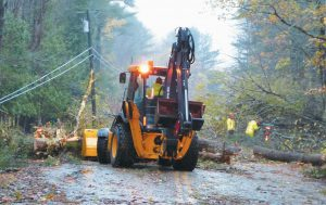 TOPSHAM FIRE AND PUBLIC WORKS CREWS cut and move debris on Foreside Road on Monday in an effort to make the road passable again.