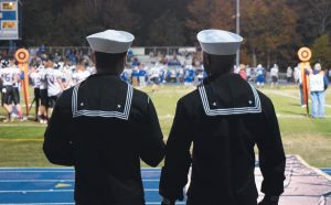 TWO CREW MEMBERS from the future USS Michael Monsoor watch the Morse High School Shipbuilders play the Freeport Falcons at Military Appreciation Night in Bath on Friday.