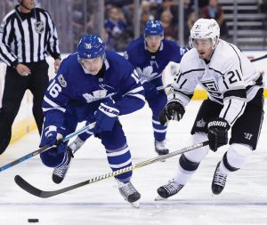 TORONTO MAPLE LEAFS center Mitchell Marner (16) carries the puck as Los Angeles Kings center Nick Shore (21) defends during the second period of an NHL hockey game in Toronto on Monday. The Maple Leafs improved to 7-2 with a 3-2 victory.