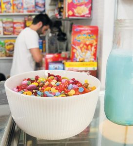 THIS PHOTO shows one of the fruity combinations of sugary cereals, topped with candy, at the El Flako cereal cafe in Barcelona, Spain. Behind it is Nicolas Castan, one of the owners, making another healthier combination.