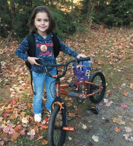 FIRST GRADER Leah Morgan stands with her bike Friday morning.