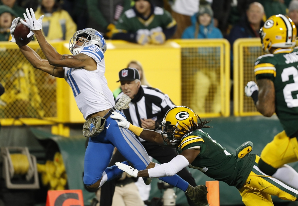 Detroit's Marvin Jones catches a touchdown pass in front of Green Bay's Davon House during the first half Monday night in Green Bay, Wisc. The Lions won, 30-17.