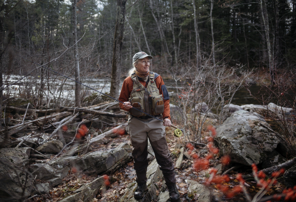 """Evelyn King stands near the bank of the Prescumpscot River in Windham. King is the founder of the Maine Women Fly Fishers and is a big advocate for getting more women out in nature. """"For me it's sharing that passion. I love the time I'm on the water and I want to help other people experience that,"""" King said."""