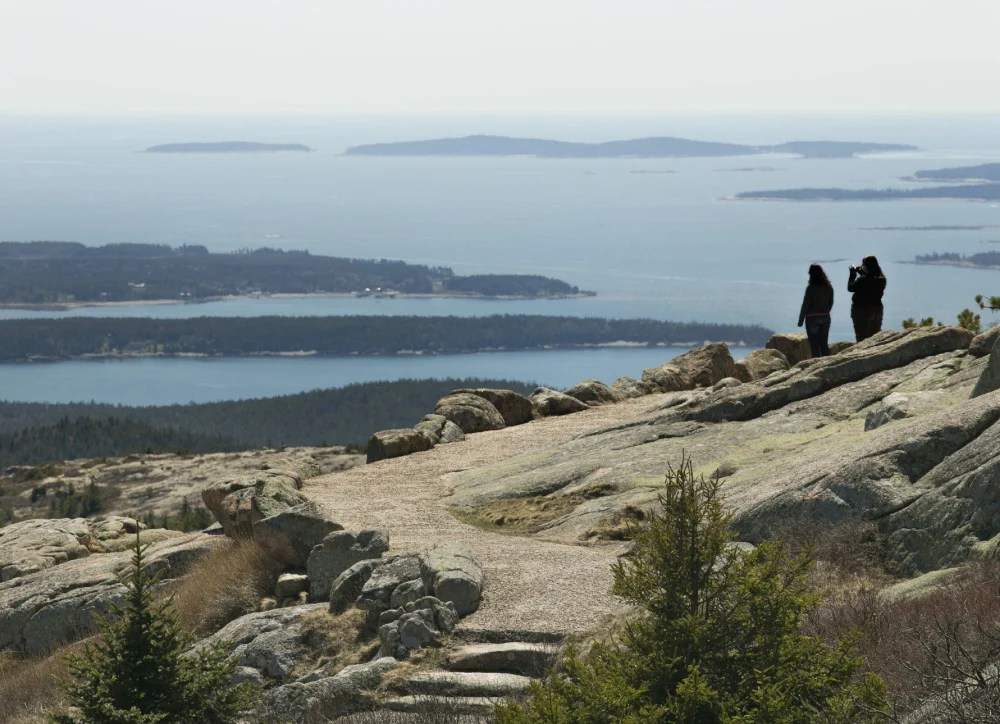 Two women take in the view from Cadillac Mountain in Acadia National Park.