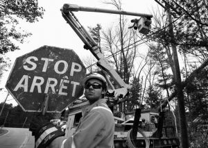 CANADIAN LINEMAN NOAH CLOWATER holds a bilingual stop sign while directing traffic while his coworkers restore power last week in Yarmouth.