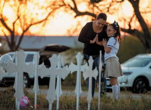 MEREDITH COOPER, of San Antonio, Texas, and her 8-year-old daughter, Heather, visit a memorial of 26 metal crosses near First Baptist Church in Sutherland Springs, Texas, Monday. The gunman of a deadly shooting at the small-town Texas church had a history of domestic violence and sent threatening text messages to his mother-in-law, a member of First Baptist, before the attack, authorities said Monday.
